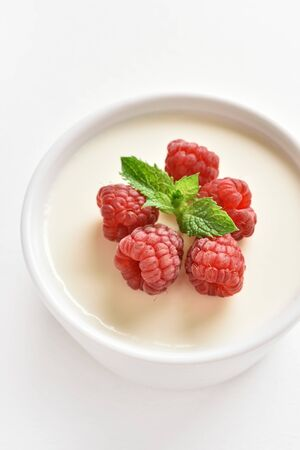 Close up of panna cotta with fresh raspberries in bowl on white stone background. Delicious dessert.