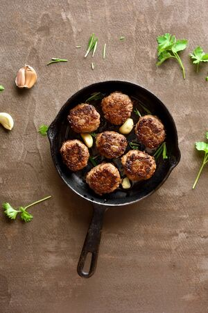 Minced meat cutlets in frying pan over brown background. Top view, flat lay Foto de archivo - 135470944