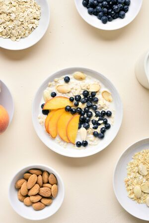 Oatmeal porridge with peach slices, almond and wild blueberries in bowl over light stone background. Healthy diet breakfast. Top view, flat lay