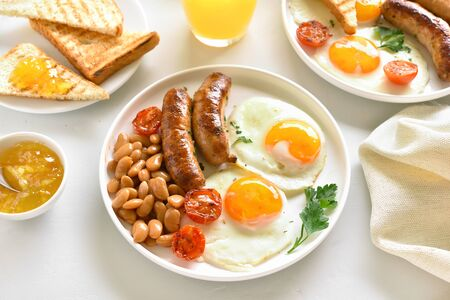 Breakfast with fried eggs, sausages, beans, tomatoes, greens on plate over white stone background