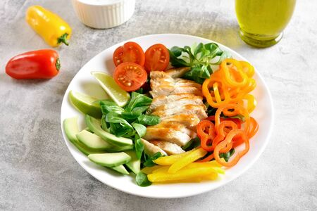 Tasty healthy vegetable salad with roasted chicken breast on stone table