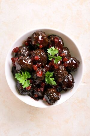 Meatballs with cranberry sauce in white bowl on light stone background. Stewed meatballs in sweet berry sauce. Top view, flat lay