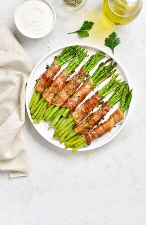 Bacon wrapped asparagus on white plate over light stone background with free text space. Top view, flat lay