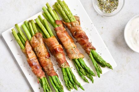 Close up of bacon wrapped asparagus on white plate over light stone background. Top view, flat lay