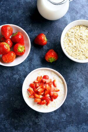 Oats porridge with strawberry in bowl over blue stone background. Tasty healthy dish for breakfast or lunch. Top view, flat lay