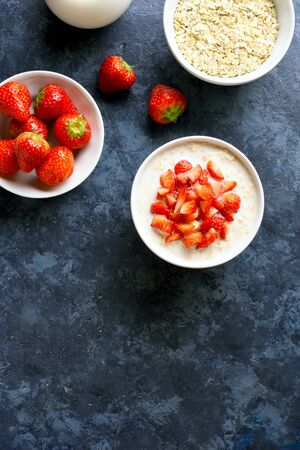 Oatmeal porridge with strawberry over blue stone background with free text space. Tasty healthy dish for breakfast or lunch. Top view, flat lay Stock Photo
