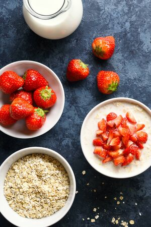 Oats porridge with strawberry and ingredients over blue stone background. Tasty healthy dish for breakfast or lunch. Top view, flat lay