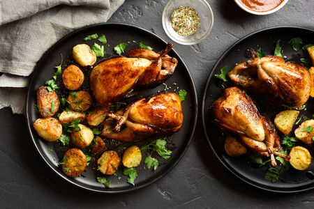 Tasty grilled quails carcasses with baked potatoes on plates over black stone background. Top view, flat lay