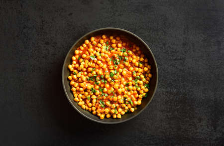 Crispy roasted chickpeas. Indian style dish over black stone background with free text space. Vegetarian vegan food concept. Top view, flat lay