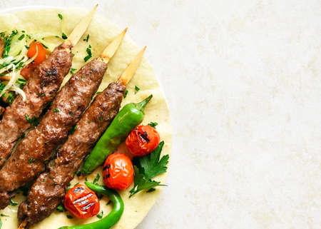 Close up of turkish Adana Kebab with fresh vegetables on flatbread over light stone background with free space. Top view, flat lay