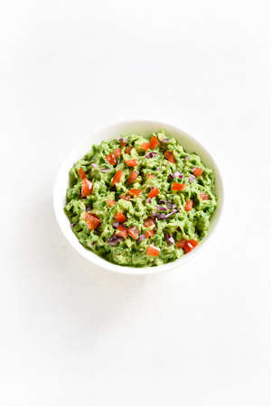 Guacamole dip in bowl over white stone background with free text space. Healthy avocado spread.
