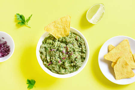 Guacamole dip in bowl over yellow background. Healthy avocado spread. Top view, flat lay