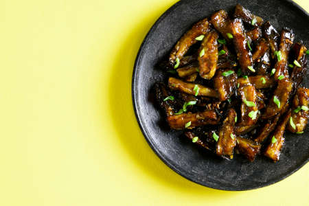 Close up of stir-fry Bulgogi Eggplant on plate over yellow background with free text space. Fried aubergine in korean style. Top view, flat lay