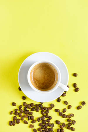 Cup of coffee espresso and coffee beans on yellow background with free text space. Top view, flat lay