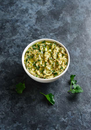 Baba ganoush (roasted eggplant dip) in bowl over blue stone background with free text space. Stock Photo