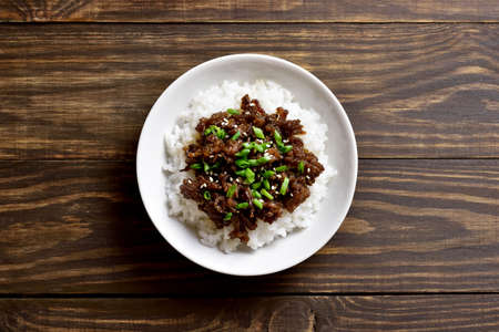 Korean ground beef and rice bowl on wooden background with free text space. Top view, flat lay