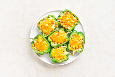 Baked green bell peppers filled with corn, carrot, cauliflower on light stone background with free space. Healthy diet or vegetarian food concept. Top view, flat lay