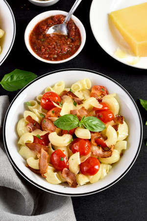 Pasta with bacon, tomato, parmesan cheese and basil leaves on plate over black stone background.
