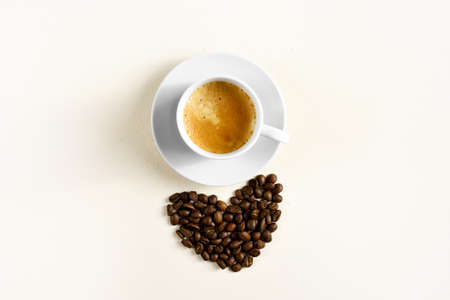 Cup of coffee espresso and coffee beans on light stone background with free text space. Top view, flat lay