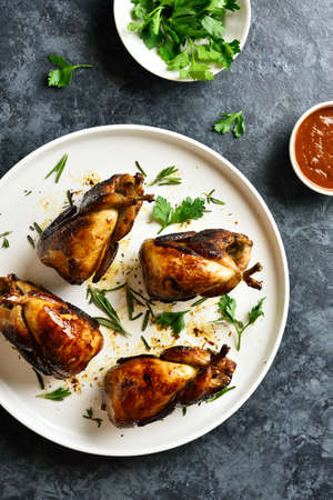 Roasted quails on white plate over blue stone background. Top view, flat lay