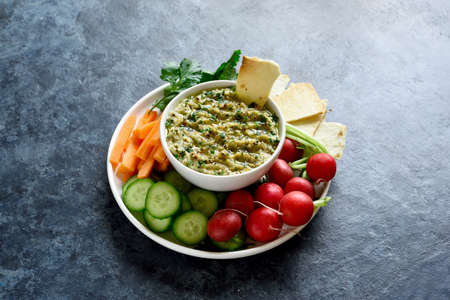 Baba ganoush (roasted eggplant dip) in bowl and fresh organic vegetables over blue stone background with free text space. Healthy eating. Vegetarian vegan food concept.