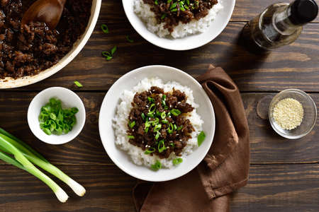 Korean ground beef and rice bowls on wooden background. Top view, flat lay Stock Photo