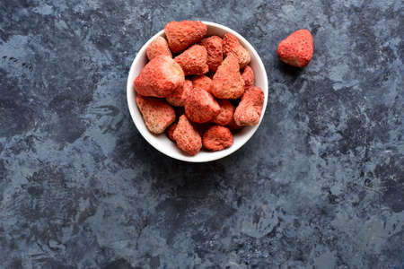 Dried strawberries in white bowl over blue stone background with free space for text. Top view, flat lay Stock Photo