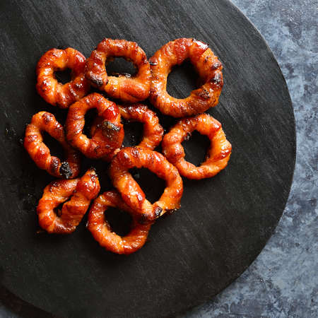 Close up of bacon wrapped onion rings on wooden board over dark stone background. Top view, flat lay