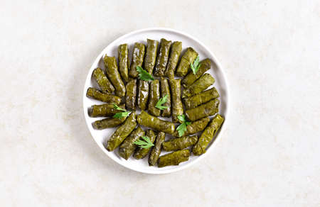 Dolma, stuffed grape leaves with rice and meat on light stone background with free text space. Top view, flat lay Stock Photo