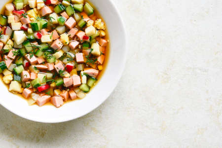 Close up traditional cold russian soup Okroshka with sausage, vegetables and kvass over light stone background with free text space. Top view, flat lay