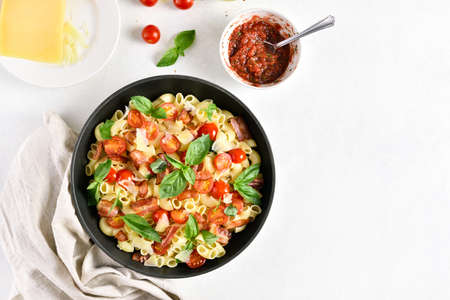 Tomato and bacon pasta with parmesan cheese and basil leaves in pan over light stone background with free text space. Top view, flat lay Stock Photo