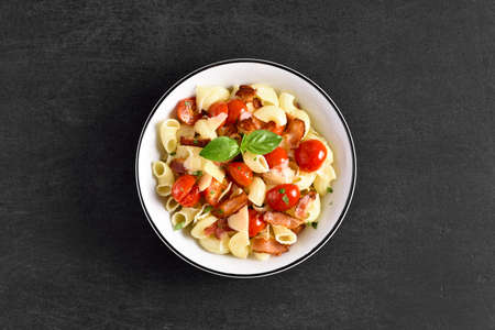 Pasta with bacon, tomato, parmesan cheese and basil leaves on plate over black stone background with free text space. Top view, flat lay