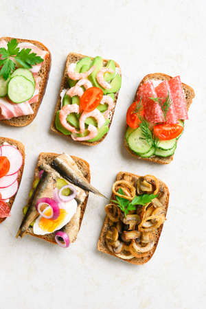 Close up of assortment open sandwiches on light stone background. Tasty healthy snack. Top view, flat lay.