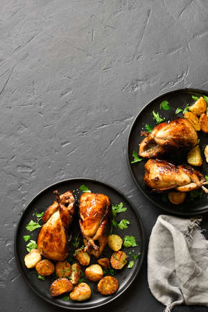 Tasty grilled quails carcasses with potato on plate over black stone background with free text space. Top view, flat lay