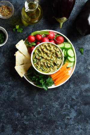 Baba ganoush (roasted eggplant dip) in bowl and fresh organic vegetables over blue stone background with free text space. Healthy eating. Vegetarian vegan food concept. Top view, flat lay
