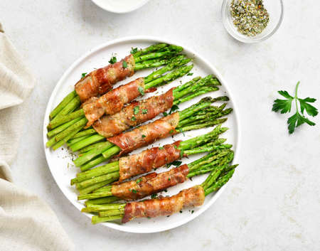 Bacon wrapped asparagus on white plate over light stone background. Top view, flat lay, close up Banque d'images
