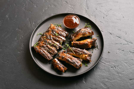 Grilled spare ribs with sauce on plate over black stone background. Close up view