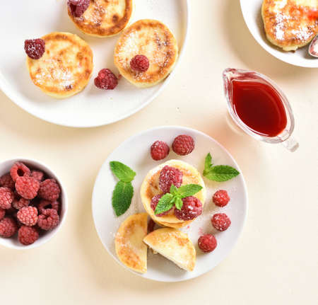 Cottage cheese pancakes with fresh raspberries on plate over light stone background. Top view, flat lay