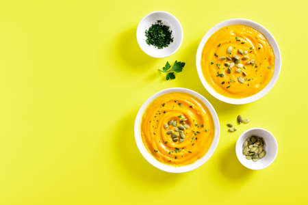 Pumpkin puree with seeds in bowl over yellow background with free text space. Healthy diet food concept. Top view, flat lay