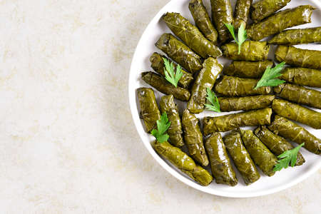 Close up view of dolma, stuffed grape leaves with rice and meat on light stone background with free text space. Top view, flat lay Imagens