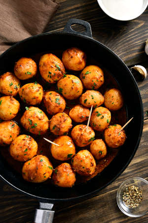 Bombay potatoes. Pan fried little baby potatoes with jeera seeds and coriander in frying pan over wooden background. Popular indian dish. Top view, flat lay
