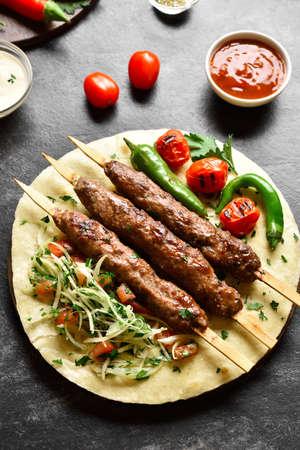 Turkish Adana Kebab with fresh vegetables on flatbread over black stone background.