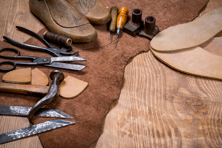 Set of leather craft tools on wooden background. Workplace for shoemaker. Piece of hide and working handmade tools on a work table. Фото со стока