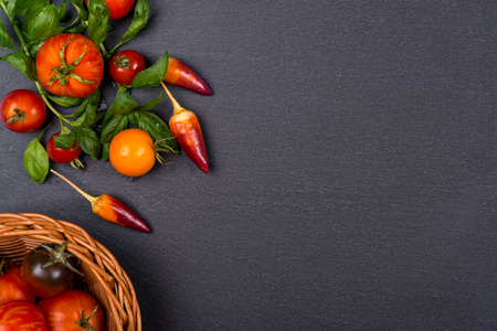 Fresh tomatoes,pepper and basil on black slate. Space for text.