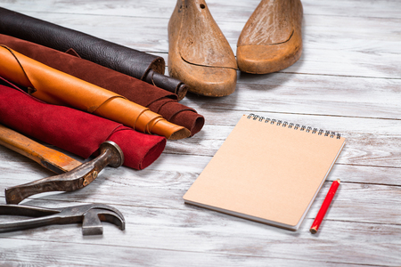 upholster: Brightly colored leather in rolls, working tools, shoe lasts, notebook with pencil on white wooden background. Leather craft.