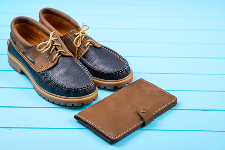 modish: Mens accessories with a brown purse and shoes. Top view on wooden background.