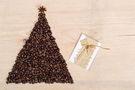 Christmas tree made from coffee beans on the wooden background. Top view, copy space.Winter holidays concept.