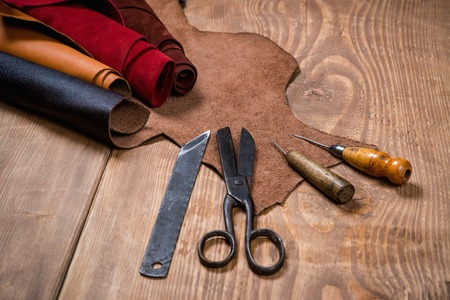 Set of leather craft tools on wooden background. Workplace for shoemaker. Piece of hide and working handmade tools on a work table. Stock Photo