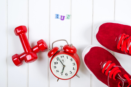 Red sneakers, clock and dumbbells on the wooden backgroyund.