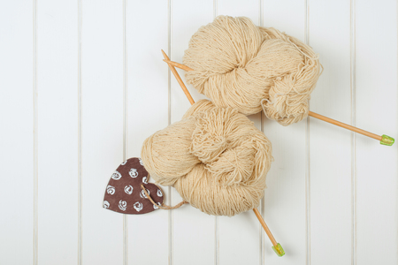 Natural woolen yarn with wood needles on the white wooden background. Stock Photo